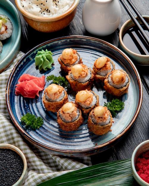 木の上の醤油を添えて皿に海老生姜とわさびの焼き寿司ロールの側面図 無料写真