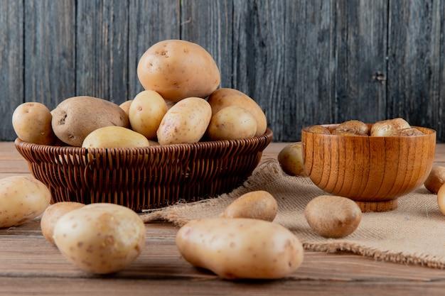 Вид сбоку корзины и чаши, полной картофеля на вретище на деревянной поверхности и фон с копией пространства Бесплатные Фотографии