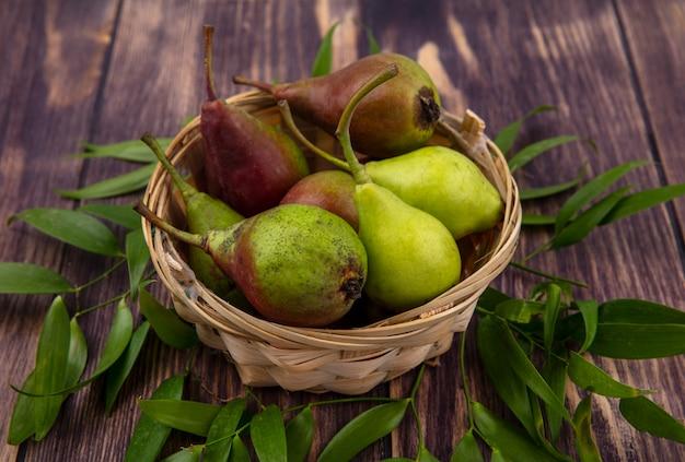 木の表面に葉と桃のバスケットの側面図 無料写真