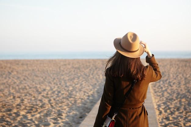 秋の砂浜に美しい女性の見知らぬ人の側面図です。ブルネットの女性の距離、海や海の気づいた船やイルカ、手で彼女のベージュの帽子を調整し、思考に満ちた心 無料写真
