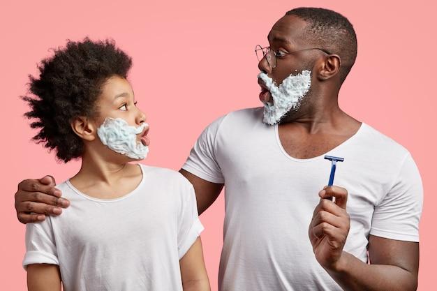 Вид сбоку на чернокожих отца и сына, которые смотрят друг на друга, у них на лицах гель для бритья, с удивленными выражениями лиц. Бесплатные Фотографии