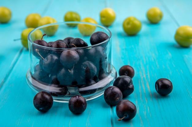 ボウルに黒ブドウの果実の側面図と青い背景に梅とブドウの果実のパターン 無料写真