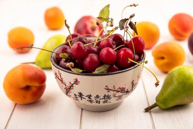 木製の背景に桃と梨のような果物のパターンでさくらんぼのボウルの側面図 無料写真