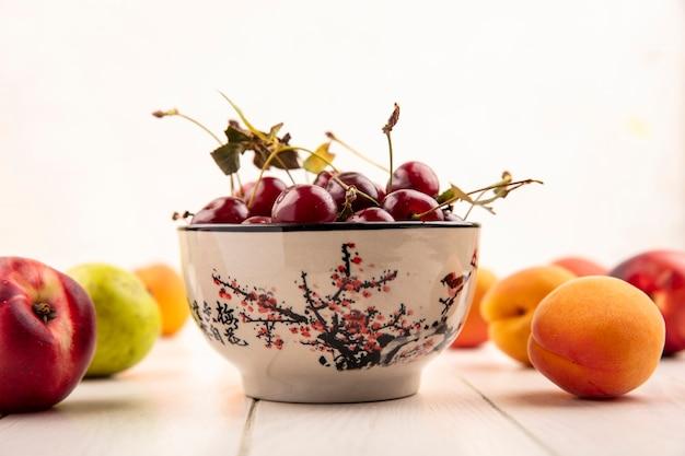 木製の表面と白い背景に桃と梨のような果物のパターンを持つサクランボのボウルの側面図 無料写真