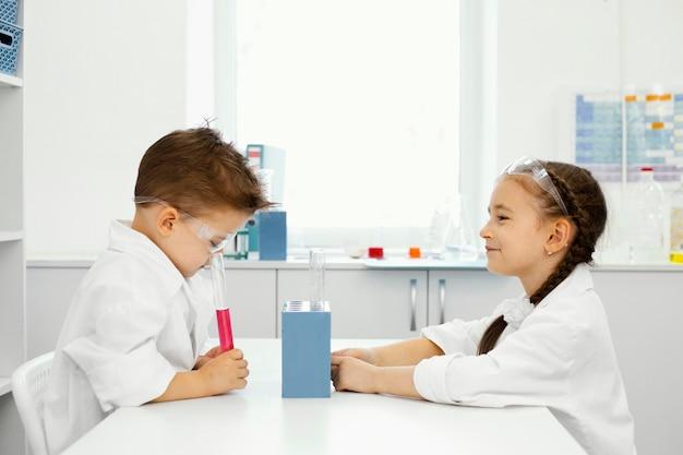 안전 안경 실험실에서 소년과 소녀 과학자의 측면보기 무료 사진