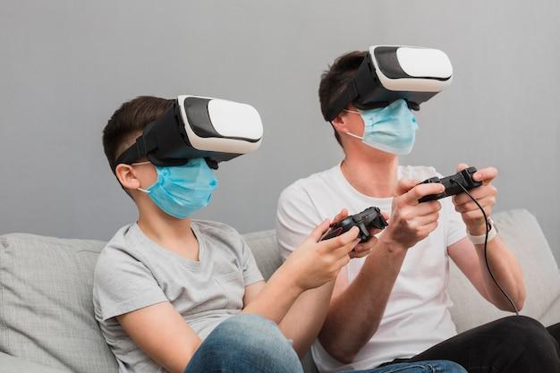 少年と医療マスクを着用しながら仮想現実のヘッドセットで遊んでいる男の側面図 無料写真