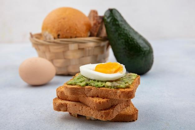 Вид сбоку хлеба с мякотью авокадо и вареным яйцом с ведром хлеба с авокадо и яйцом на белой поверхности Бесплатные Фотографии