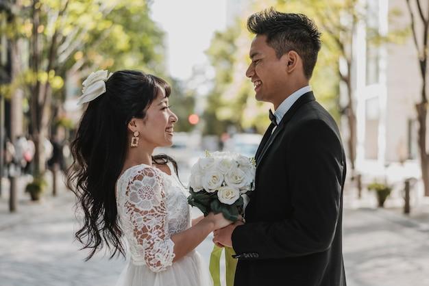 신부와 신랑의 거리에서 포즈의 측면보기 무료 사진
