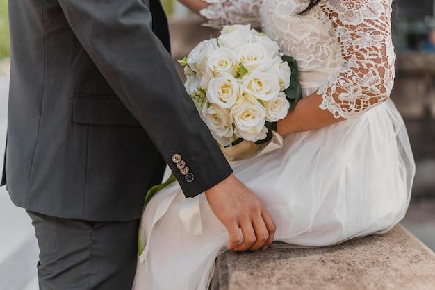꽃의 부케와 신부와 신랑의 측면보기 프리미엄 사진