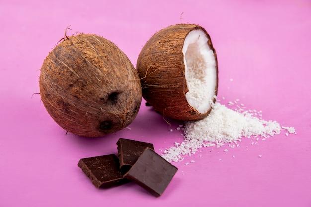 ピンクの表面にココナッツパウダーとチョコレートバーと茶色と新鮮なココナッツの側面図 無料写真