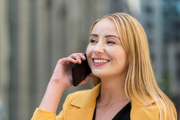 スマートフォンで話している女性実業家の側面図 無料写真