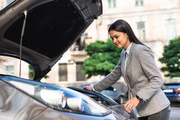 Деловая женщина, проверяющая двигатель автомобиля, вид сбоку Бесплатные Фотографии