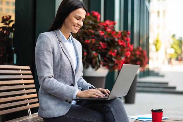 コーヒーを飲みながら屋外でラップトップを使用して実業家の側面図 無料写真