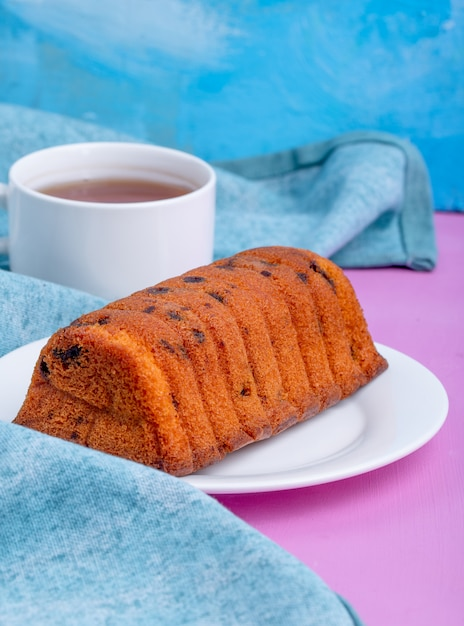 白い皿にレーズンと青と紫の背景にお茶のカップのケーキの側面図 無料写真