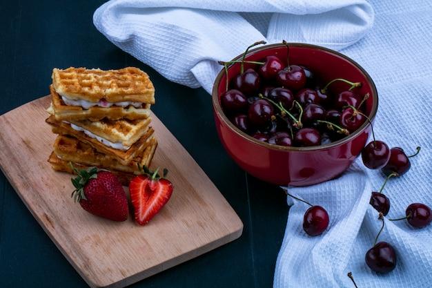 黒の背景に布の上のボウルにチェリーとまな板の上のケーキとイチゴの側面図 無料写真