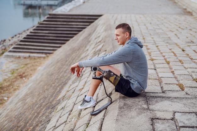 スポーツウェアと岸壁に座って川を見て義足で白人の障害を持つスポーツマンの側面図です。 Premium写真