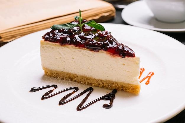 Вид сбоку чизкейк с вишневым желе на вершине на белой тарелке Бесплатные Фотографии