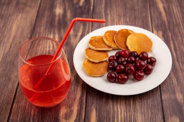 ガラスの飲用チューブと木製の背景にパンケーキとチェリーのプレートとチェリージュースの側面図 無料写真