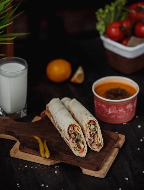 Вид сбоку куриного донера, завернутого в лаваш на деревянной доске, подается с супом из липы и айранским напитком на столе Бесплатные Фотографии