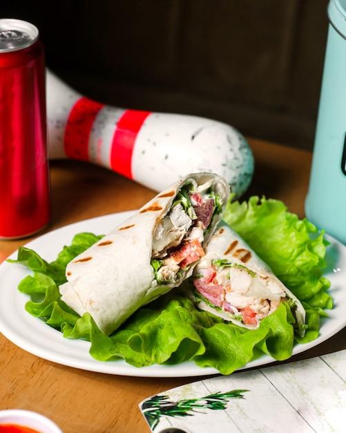 Вид сбоку курица донер, завернутые в лаваш на салат на деревянный стол Бесплатные Фотографии