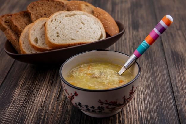 木製の背景にボウルにスライスしたライ麦白茶色の種の穂軸のものとしてボウルとパンのスプーンでチキンオルゾスープの側面図 無料写真