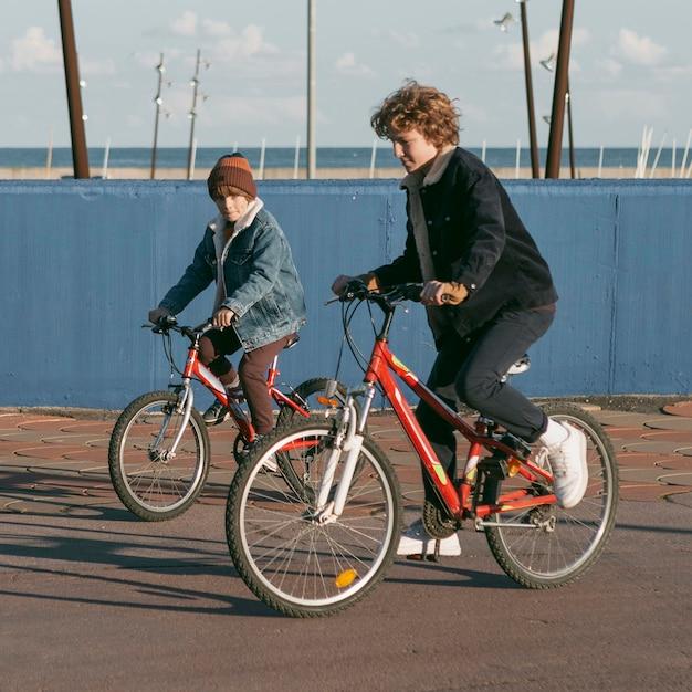 자전거에 야외에서 자식 친구의 측면보기 무료 사진