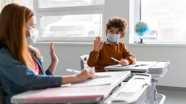 Вид сбоку на детей с медицинскими масками в классе, приветствующих друг друга на расстоянии Бесплатные Фотографии