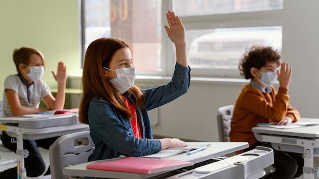 学校で学習している医療マスクを持つ子供の側面図 無料写真