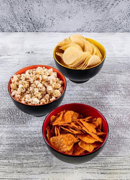 Вид сбоку чипсов и попкорна в мисках на белом деревянном вертикальном столе Бесплатные Фотографии