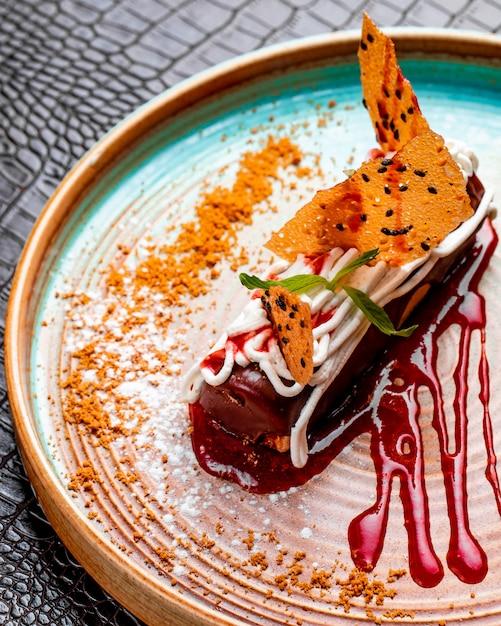 Вид сбоку шоколадного эклера со взбитыми сливками и клубникой на тарелке, украшенной ягодным сиропом и сахарной пудрой Бесплатные Фотографии