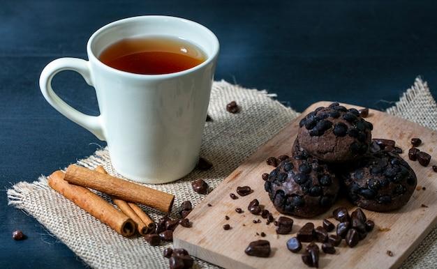 荒布と青の背景にお茶とシナモンのカップとまな板の上のクッキーとチョコレートの側面図 無料写真