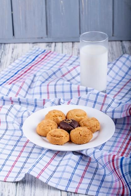 Вид сбоку печенье на белой тарелке подается со стаканом молока Бесплатные Фотографии