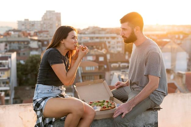Вид сбоку пара, едящая пиццу на открытом воздухе Бесплатные Фотографии