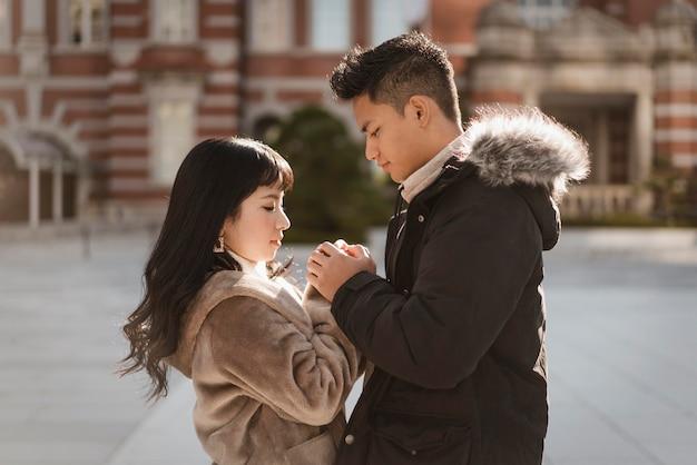 Вид сбоку пара, взявшись за руки на открытом воздухе в городе Бесплатные Фотографии
