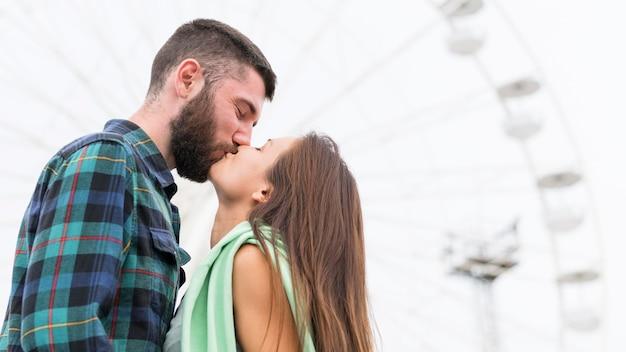 屋外でキスするカップルの側面図 無料写真
