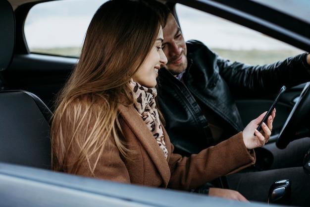 Вид сбоку пара с помощью смартфона в машине Бесплатные Фотографии