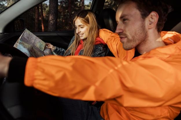 Вид сбоку пара с картой в машине, отправляющейся в поездку Бесплатные Фотографии