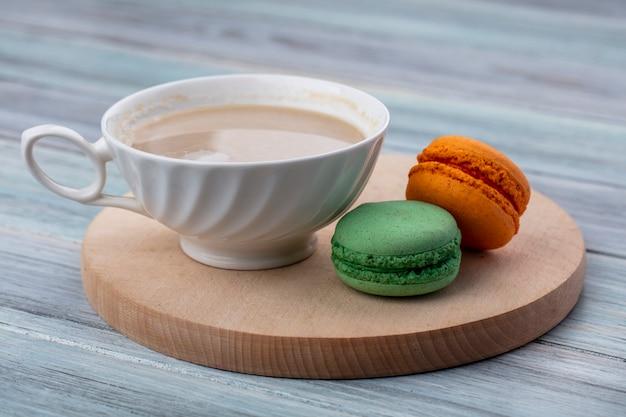 灰色の表面に木製のスタンドに色のマカロンとカプチーノカップの側面図 無料写真