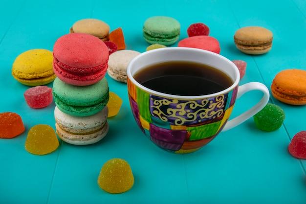 青の背景に一杯のコーヒーとクッキーのサンドイッチの側面図 無料写真