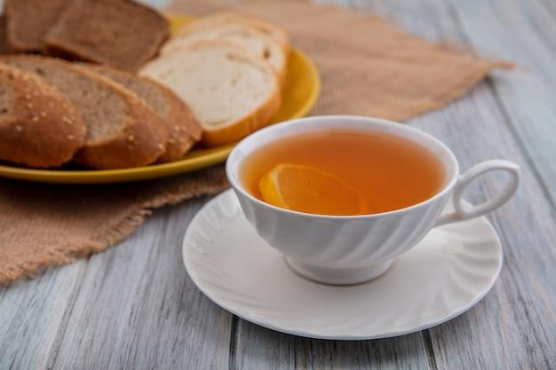 Вид сбоку чашки горячего пунша на блюдце с нарезанным хлебом в тарелке на вретище на деревянном фоне Бесплатные Фотографии