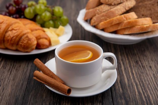 Вид сбоку чашки горячего тодди с корицей на блюдце и круассанов с виноградом и ломтиками сыра и хлебом в тарелках на деревянном фоне Бесплатные Фотографии