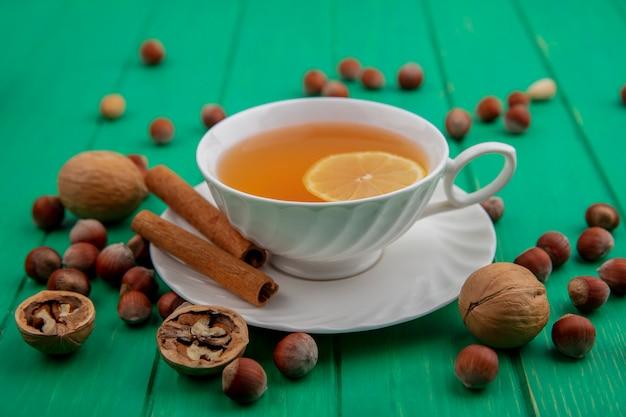 Вид сбоку чашки горячего тодди с лимоном внутри и корицей на блюдце с орехами и грецкими орехами на зеленом фоне Бесплатные Фотографии
