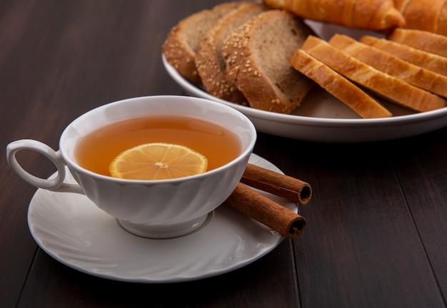 Вид сбоку чашки горячего тодди с лимоном внутри и корицей на блюдце с нарезанным хлебом в тарелке на деревянном фоне Бесплатные Фотографии