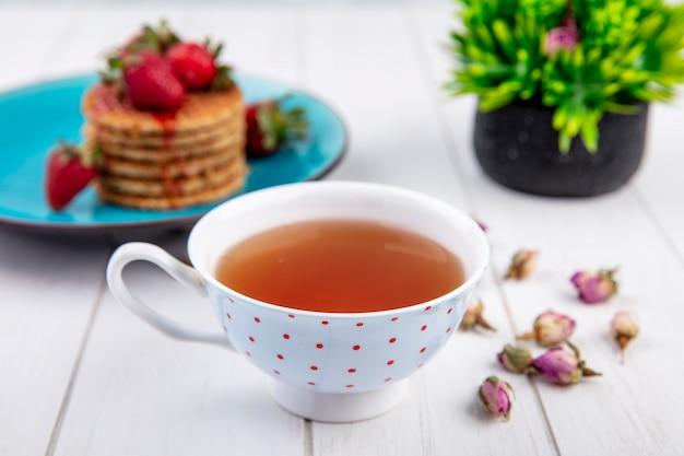 Вид сбоку чашку чая и вафельные печенье с клубникой в тарелку и цветы на деревянной поверхности Бесплатные Фотографии