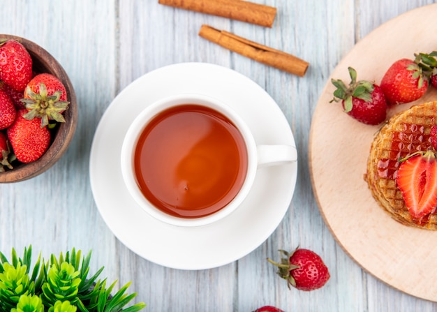 Вид сбоку чашки чая на блюдце и вафельные печенье с клубникой в тарелку и миску с корицей на деревянной поверхности Бесплатные Фотографии