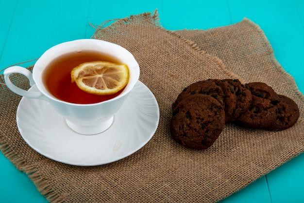 Вид сбоку чашки чая на блюдце с ломтиком лимона и печенье на вретище и синем фоне Бесплатные Фотографии