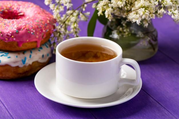 Вид сбоку на чашку чая с пончиками и цветами на ярко-фиолетовой поверхности Бесплатные Фотографии
