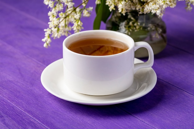Вид сбоку чашки чая с цветами на ярко-фиолетовой поверхности Бесплатные Фотографии
