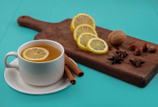 レモンスライスとシナモンとナッツとクルミスライスレモンとまな板の青い背景の上のお茶の側面図 無料写真