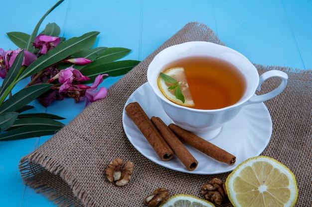 花と荒布を着たくるみレモンスライスとクルミとソーサーにレモンスライスとシナモンとお茶のカップの側面図し、青の背景に葉 無料写真
